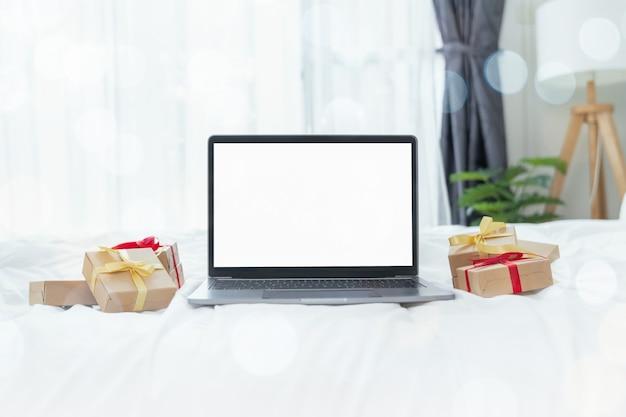 モックアップの白い画面と白い背景の上のギフトボックスとラップトップ。メリークリスマスのコンセプト。