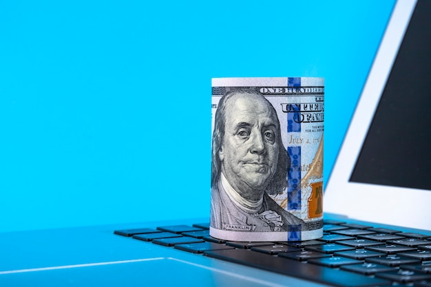 파란색 배경에 종이 100 달러 지폐의 롤과 노트북. 공간을 복사하십시오.