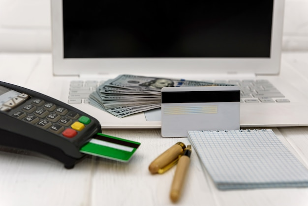 Laptop with banking terminal and dollar banknotes