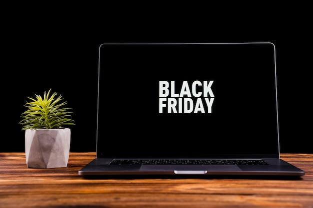 デスクトップ上の黒い金曜日メッセージとラップトップ Premium写真