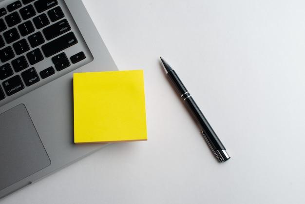 机の上の黄色のメモ帳と黒のペンでノートパソコン