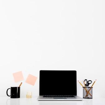 Laptop with blank black screen on desk in office
