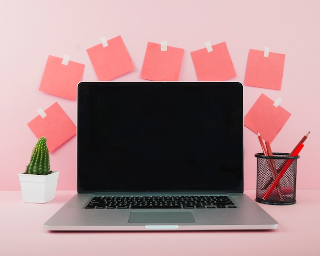 Laptop with blank black screen on pink office desk
