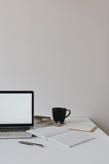 コーヒーカップ、白い壁に紙のシートとテーブルの上の空白のコピースペースのモックアップ画面とラップトップ。