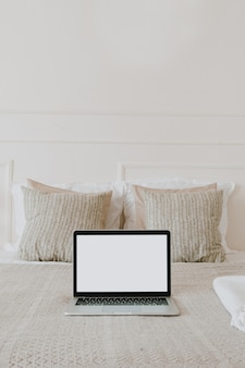 Laptop with blank copy space screen display in bed with plaid, pillows against white wall
