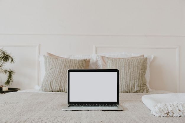 空白のコピースペーススクリーンディスプレイ付きのラップトップは、白い壁に格子縞の枕を備えたベッドに表示されます。美的な朝の構図。