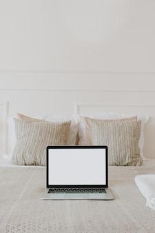 格子縞のベッド、白い壁に枕の空白のコピースペース画面ディスプレイを備えたラップトップ