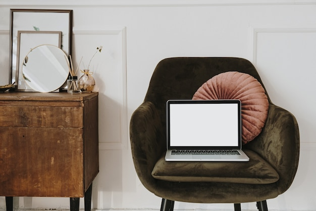 Laptop with blank copy space screen display on lounge chair with pillow against white wall