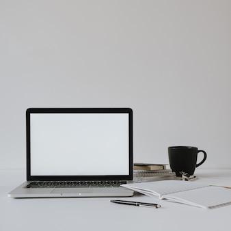 コーヒーカップ、白い壁に紙のシートとテーブルの上の空白のコピースペース画面とラップトップ