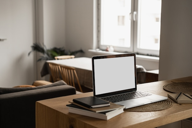 木製のテーブルにノートブックとテーブルの上の空白のコピースペース画面とラップトップ