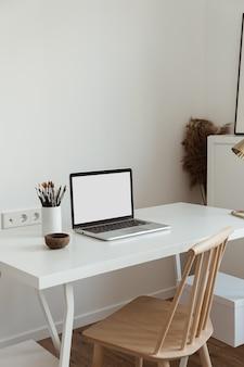 白い壁にテーブルの上の文房具とテーブルの上の空白のコピースペース画面とラップトップ