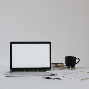 Laptop with blank copy space screen on table with coffee cup, paper sheet against white wall