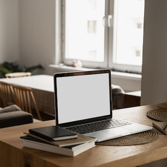 Laptop with blank copy space screen on table with notebooks on wooden table