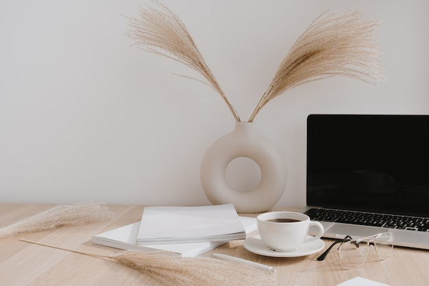 Laptop with blank copy space screen on table with pampas grass bouquet in vase, glasses, magazines and coffee cup.