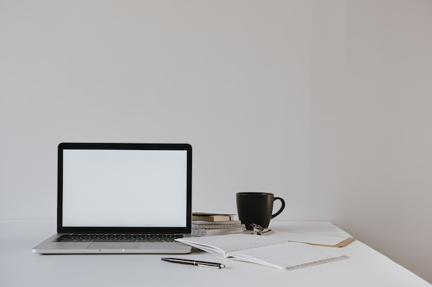 Laptop with blank copy space on table with coffee cup, paper sheet, stationery against white wall