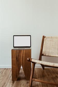 빈 모형 복사 공간 화면 노트북입니다. 등나무 나무 의자와 현대적인 인테리어 디자인 개념.