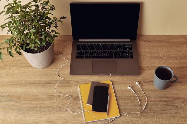 Ноутбук с пустым экраном и наушниками, растение в горшке, кружка, желтый блокнот, ручка, мобильный телефон.