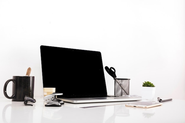 Laptop with blank screen and cellphone on reflective desk