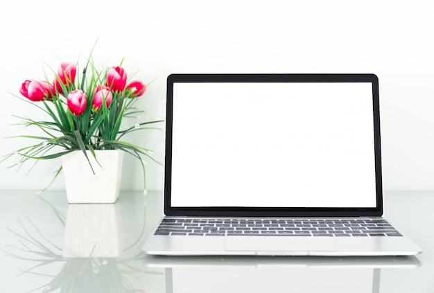 Laptop with blank screen and coffee cup with flower