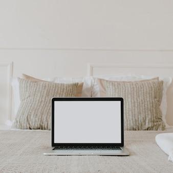 ベッドに空白の画面を表示するノートパソコン