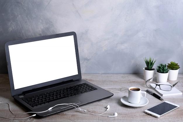Компьтер-книжка с пустым экраном для монтажа графического дисплея. компьютер на деревянном сером столе в комнате офиса.