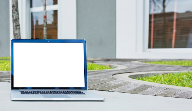 Laptop with blank screen in front of house