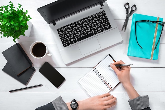 Laptop with blank screen and girl's hands. flat lay, top view workspace. copy space