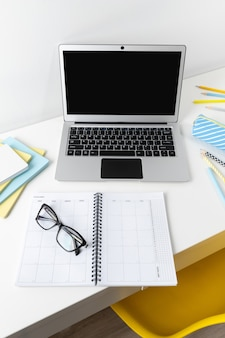 Laptop with blank screen glasses and stationery on white modern table