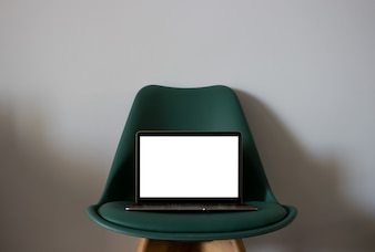 Laptop with blank screen on chair