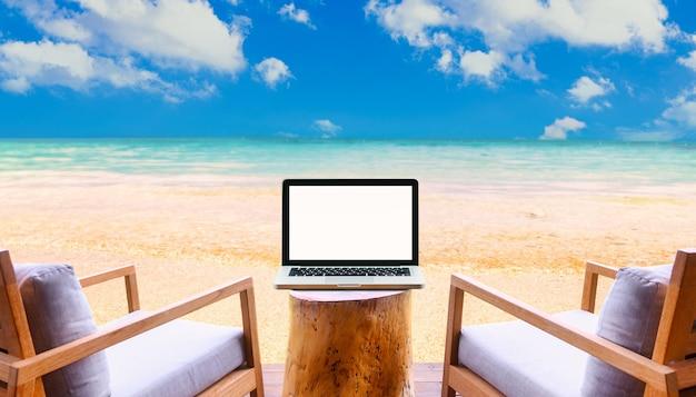 Ноутбук с пустым экраном на столе с красивым пляжем и тропическим морем