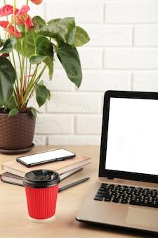 テーブルの上の空白の画面とラップトップ