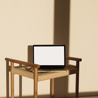 벽에 햇빛 그림자에 고리 버들 세공 벤치에 빈 화면이 노트북