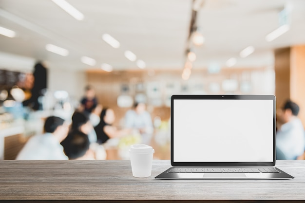 Laptop with blank screen placed on table blurred people meeting