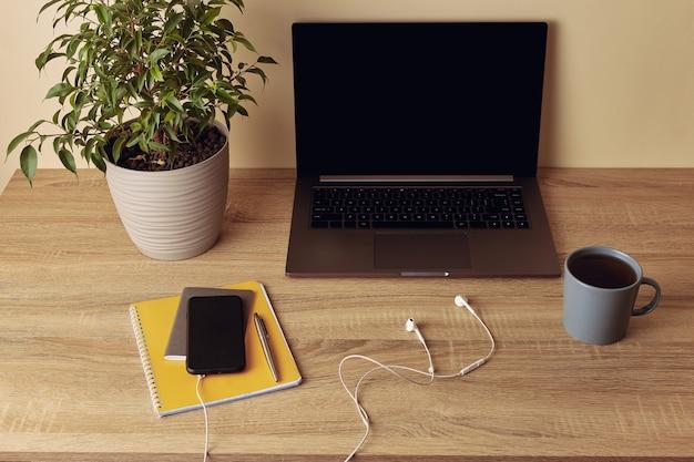 Ноутбук с пустой экран, растение в горшке, кружка, желтый блокнот, ручка, мобильный телефон и наушники.
