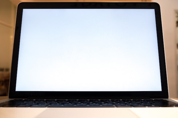 Laptop with blank screen on table of coffee shop blur background with bokeh. keyboard, use in traditional chinese alphabet operating system.