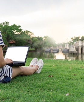 Laptop with blank screen of woman lifestyle sitting at the park