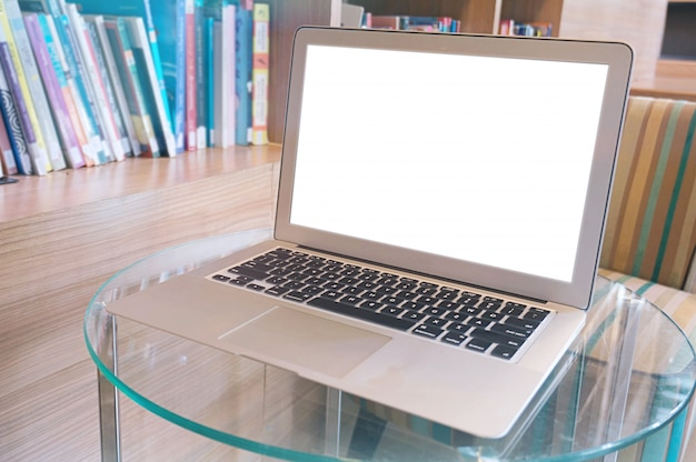 Laptop with blank screen on wooden table in front of library - technology concept