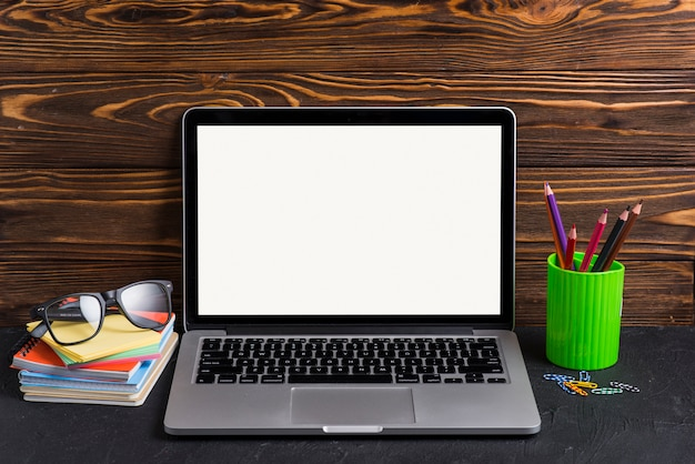 Laptop with blank white screen; books; eyeglasses; pencil holders and paperclip on wooden desk