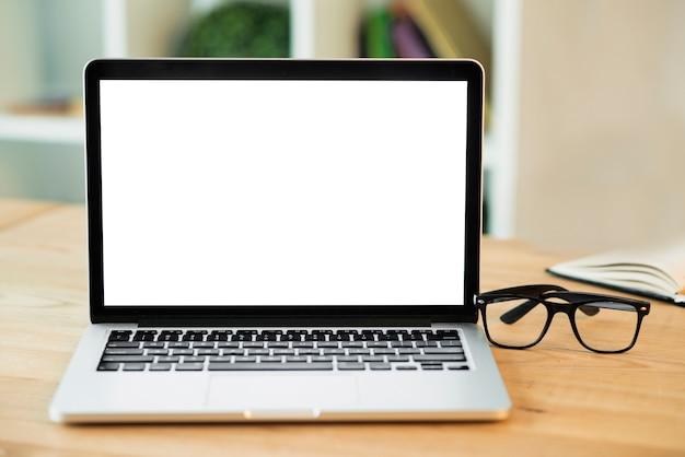 Laptop with blank white screen and eyeglasses on wooden desk