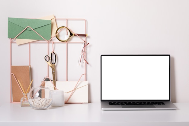 Laptop with blank white screen on office desk interior. stylish gold workplace mockup table view.