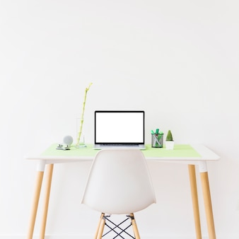 Laptop with blank white screen on desk in front of wall