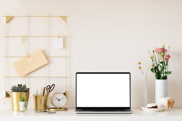 Ноутбук с пустым белым экраном на интерьере офисного стола. вид таблицы макета стильного золотого рабочего места.