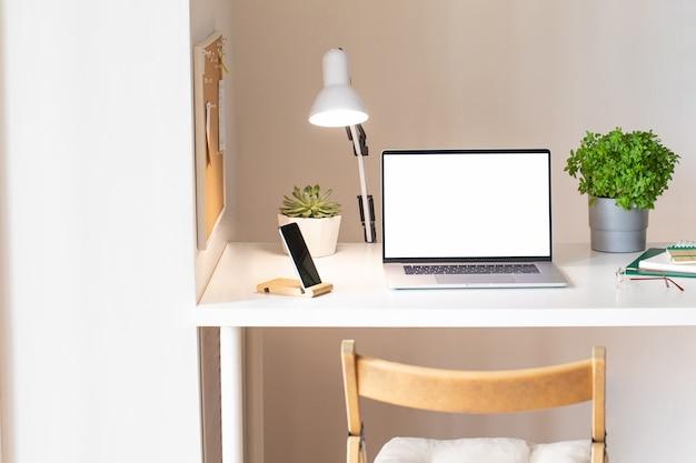 Ноутбук с пустым белым экраном на интерьере офисного стола. вид таблицы макета рабочего места стильного розового золота.