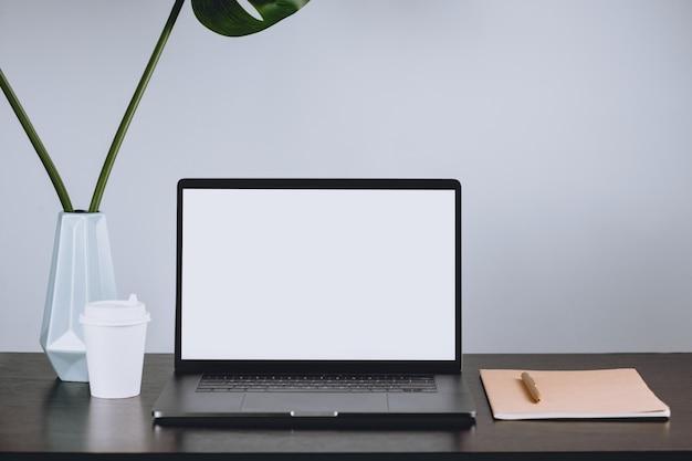 Ноутбук с пустым белым экраном на столе