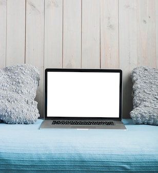 Laptop with blank white screen and pillow on sofa