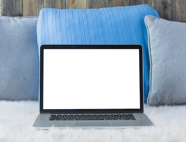 Laptop with blank white screen on sofa