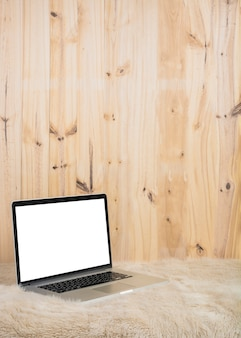 Laptop with blank white screen on soft fur in front of wooden wall