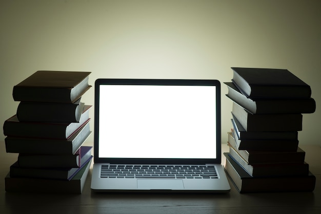 Laptop with bright screen between mountains of books