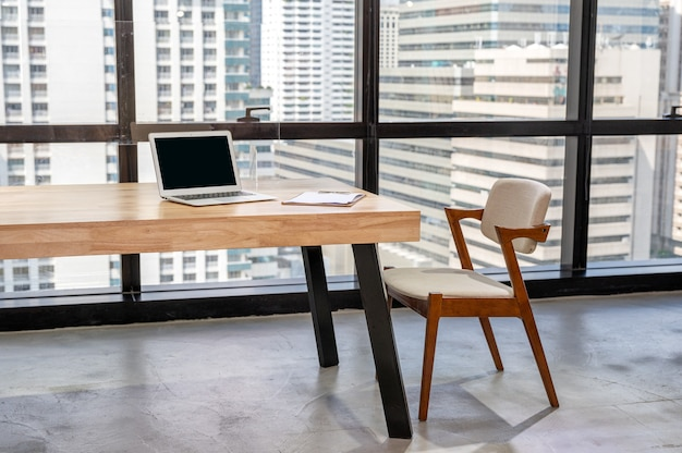 Laptop with business document on wooden desk and chair in the office