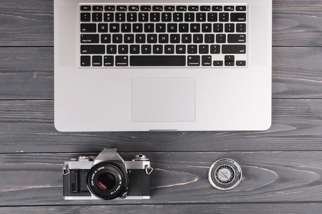 카메라와 나무 테이블에 나침반 노트북
